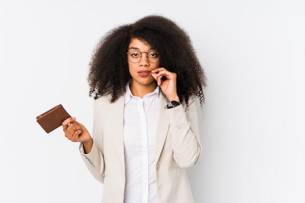 Mulher de negócios afro jovem segurando um carro de crédito isolado mulher de negócios afro jovem segurando um carro de crédito com os dedos nos lábios, mantendo um segredo.