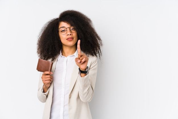 Mulher de negócios afro jovem segurando um carro de crédito isolado mulher de negócios afro jovem segurando um cartão de crédito número um com o dedo.
