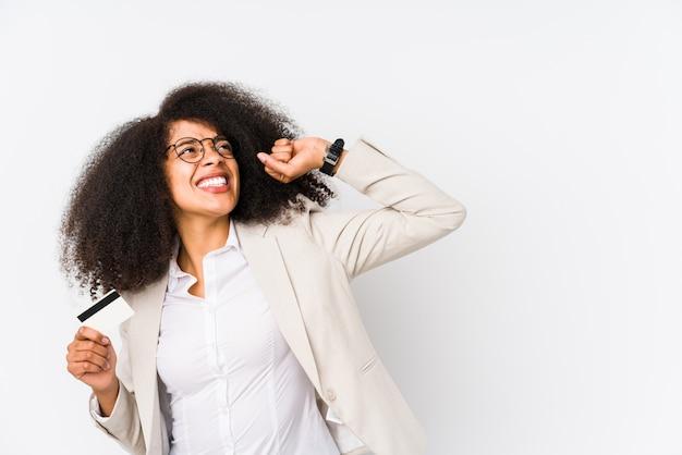 Mulher de negócios afro jovem segurando um carro de crédito isolado mulher de negócios afro jovem segurando um punho de levantamento de crédito após uma vitória, conceito vencedor.