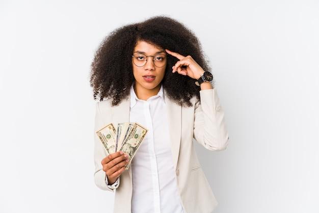 Mulher de negócios afro jovem segurando um carro de crédito isolado mulher de negócios afro jovem segurando um templo de carpointing de crédito com o dedo, pensando, focado em uma tarefa.
