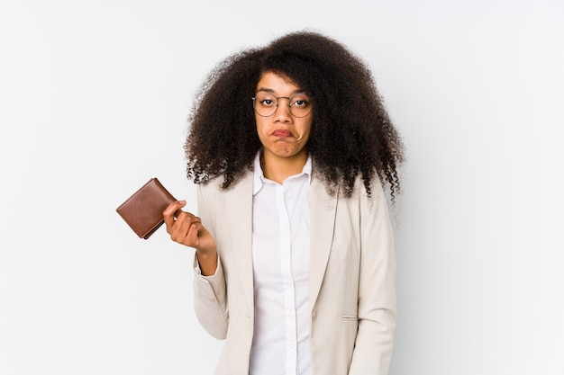 Mulher de negócios afro jovem segurando um cartão de crédito encolhe os ombros e abre os olhos confusos.