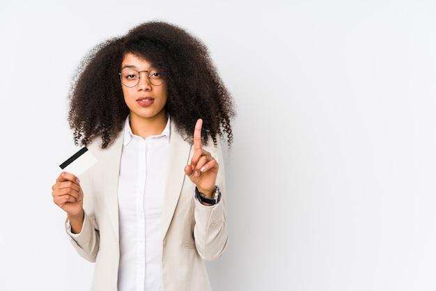 Mulher de negócios afro jovem segurando um cartão de crédito