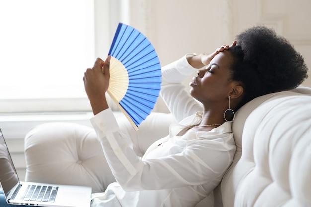 Mulher de negócios afro sofrendo de insolação, sentada na sala de estar em casa, usando um ventilador