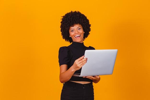 Mulher de negócios afro trabalhando online com o computador portátil.