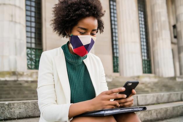 Mulher de negócios afro usando máscara protetora e usando o telefone celular enquanto está sentada em escadas ao ar livre na rua