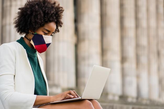 Mulher de negócios afro usando máscara protetora e usando seu laptop enquanto está sentado na escada ao ar livre. conceito urbano e empresarial.