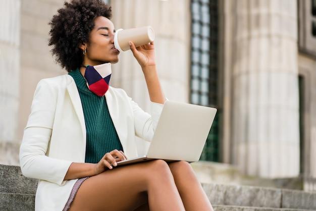 Mulher de negócios afro usando seu laptop e bebendo café enquanto está sentado na escada ao ar livre. conceito urbano e empresarial.