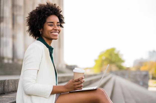 Mulher de negócios afro usando seu laptop enquanto está sentado na escada ao ar livre. conceito urbano e empresarial. Foto Premium