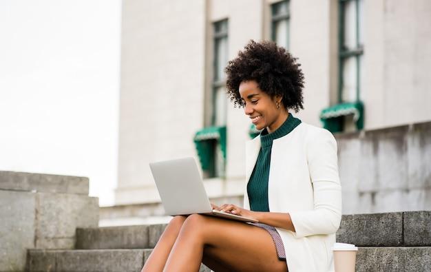 Mulher de negócios afro usando seu laptop enquanto está sentado na escada ao ar livre. conceito urbano e empresarial.