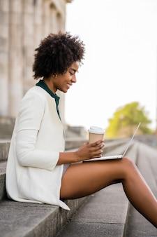 Mulher de negócios afro usando seu laptop enquanto está sentado na escada ao ar livre.