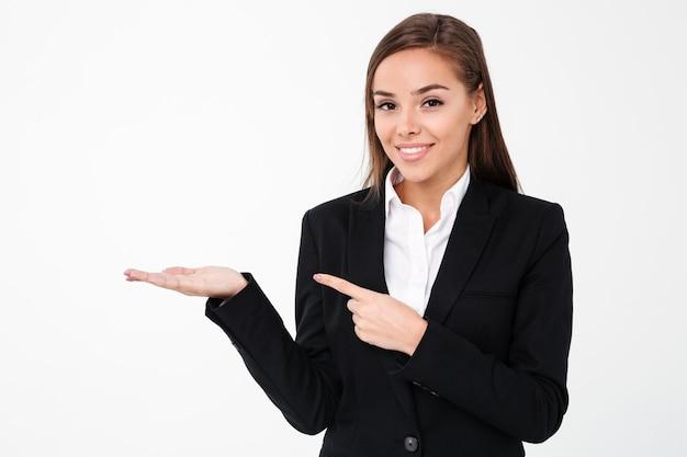 Mulher de negócios alegre apontando para copyspace.