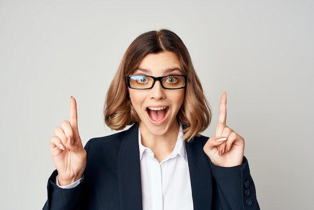 Mulher de negócios alegre de terno gesticulando com as mãos no trabalho oficial