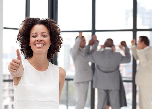 Mulher de negócios alegre fazendo um thum-up com seus colegas