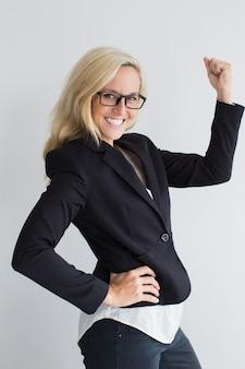 Mulher de negócios alegre que mostra o gesto vencedor