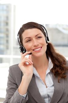 Mulher de negócios alegre usando o fone de ouvido sentado em sua mesa