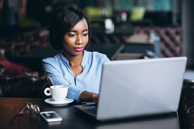 Mulher de negócios americano africano com laptop em um café