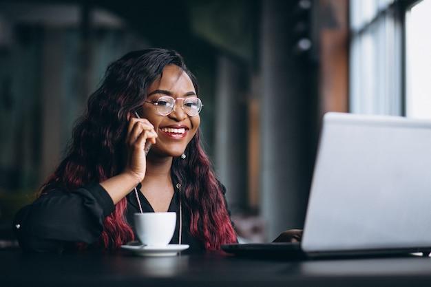 Mulher de negócios americano africano com telefone e laptop