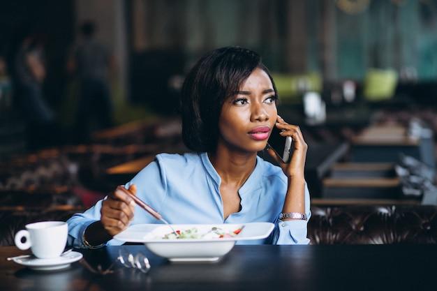 Mulher de negócios americano africano com telefone e salada