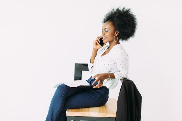 Mulher de negócios americano africano jovem falando ao telefone enquanto está sentado na cadeira