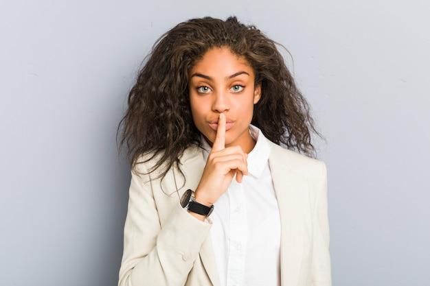 Mulher de negócios americano africano jovem mantendo um segredo ou pedindo silêncio.