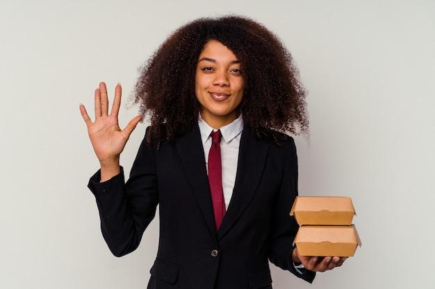 Mulher de negócios americano africano jovem segurando um hambúrguer isolado na parede branca, sorrindo alegre mostrando o número cinco com os dedos.
