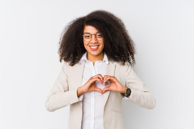 Mulher de negócios americano africano jovem sorrindo e mostrando uma forma de coração com as mãos.