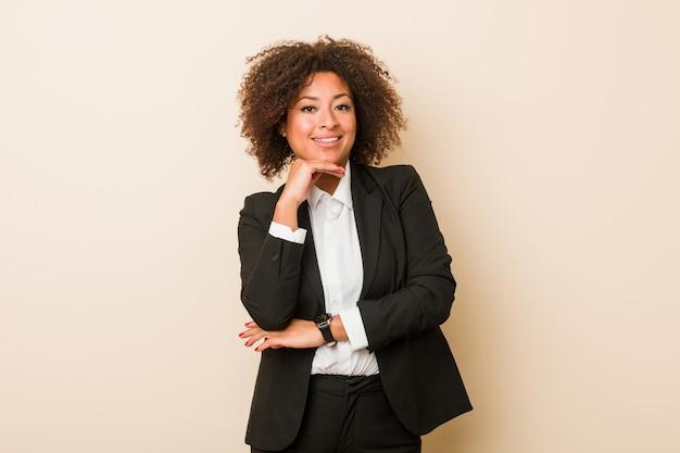 Mulher de negócios americano africano jovem sorrindo feliz e confiante, tocando o queixo com a mão.