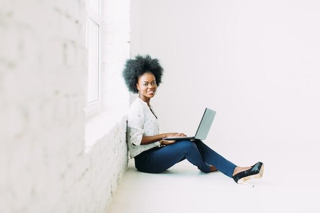 Mulher de negócios americano africano jovem usando o laptop, enquanto está sentado no chão perto de uma grande janela