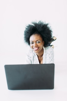 Mulher de negócios americano africano jovem usando o laptop, enquanto estava deitado no chão, isolado