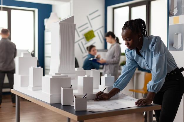Mulher de negócios americano africano no escritório de arquitetura, trabalhando na planta da construção jovem de mesa.