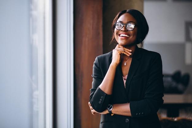 Mulher de negócios americano africano pela janela