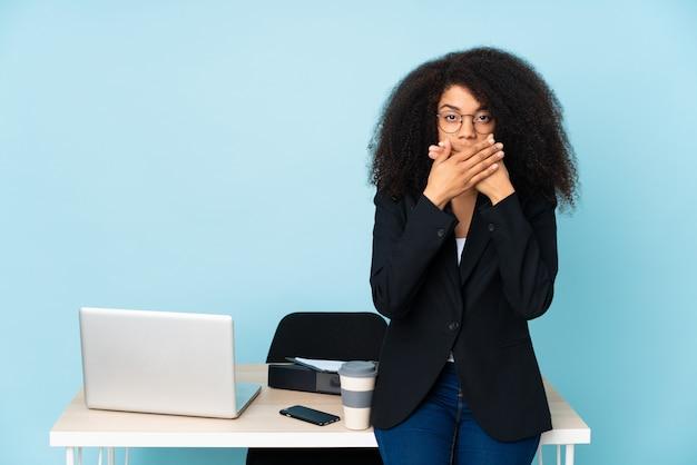 Mulher de negócios americano africano trabalhando em seu local de trabalho boca coning com as mãos