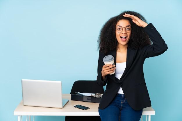 Mulher de negócios americano africano trabalhando em seu local de trabalho com expressão de surpresa