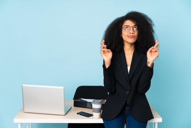 Mulher de negócios americano africano trabalhando em seu local de trabalho com os dedos cruzando e desejando o melhor