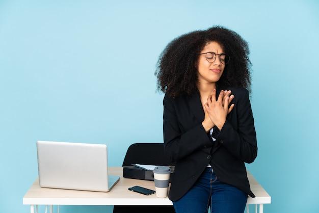 Mulher de negócios americano africano trabalhando em seu local de trabalho com uma dor no coração