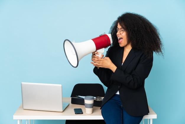 Mulher de negócios americano africano trabalhando em seu local de trabalho gritando através de um megafone