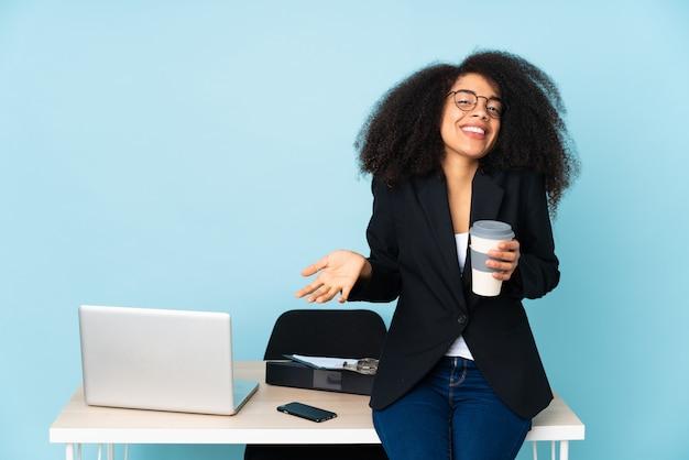 Mulher de negócios americano africano trabalhando em seu local de trabalho sorrindo