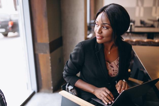Mulher de negócios americano africano trabalhando em um computador em um bar
