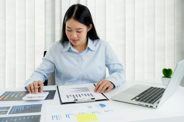 Mulher de negócios analisa o gráfico e realiza videoconferência com laptop no escritório em casa para definir metas de negócios desafiadoras