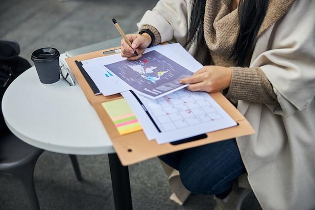 Mulher de negócios analisando transferências comerciais globais em um café ao ar livre