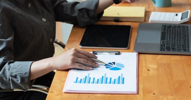 Mulher de negócios, analisar e discutir sobre o documento gráfico de negócios.
