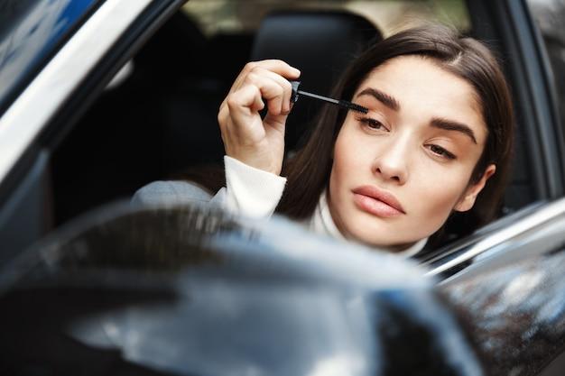 Mulher de negócios aplicando rímel e olhando no espelho retrovisor, maquiar-se a caminho da reunião de negócios