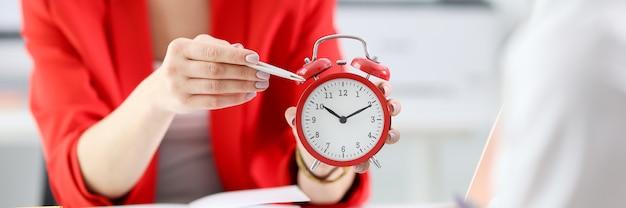 Mulher de negócios aponta com caneta para colega no despertador vermelho. gestão do tempo nos negócios