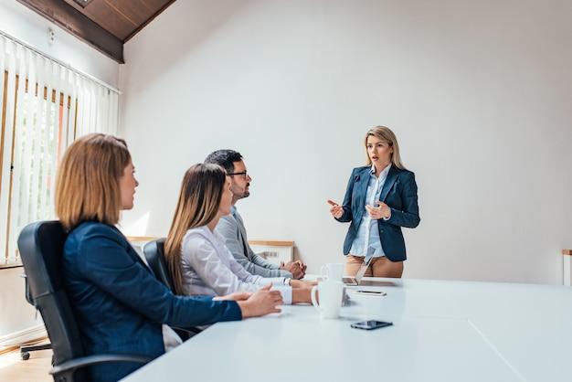 Mulher de negócios apresentando aos colegas em uma reunião. copie o espaço.