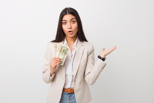 Mulher de negócios árabe jovem segurando dólares impressionados