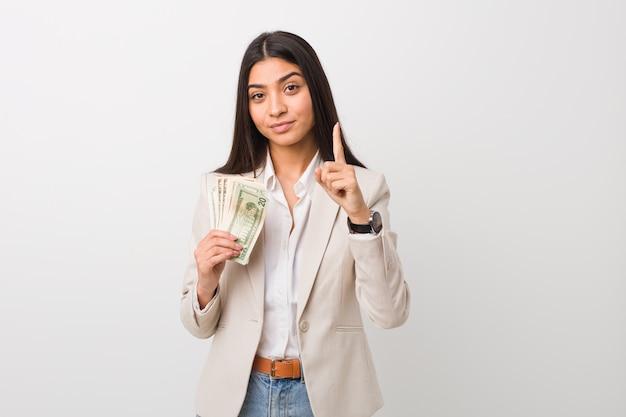 Mulher de negócios árabe jovem segurando dólares mostrando o número um com o dedo.
