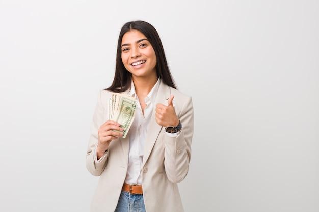 Mulher de negócios árabe jovem segurando dólares sorrindo e levantando o polegar