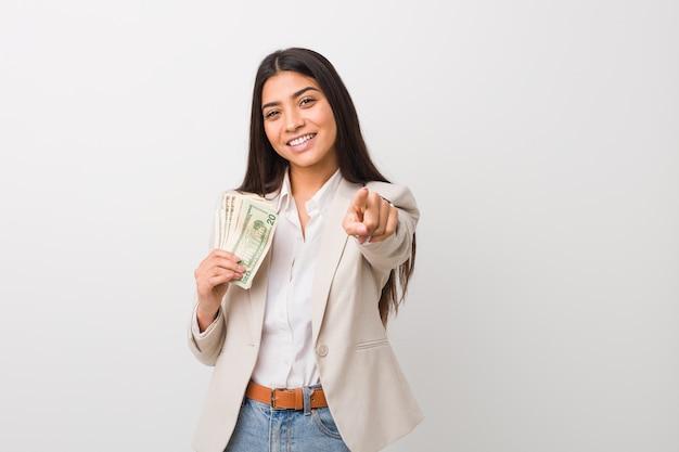 Mulher de negócios árabe jovem segurando sorrisos alegres de dólares, apontando para a frente.