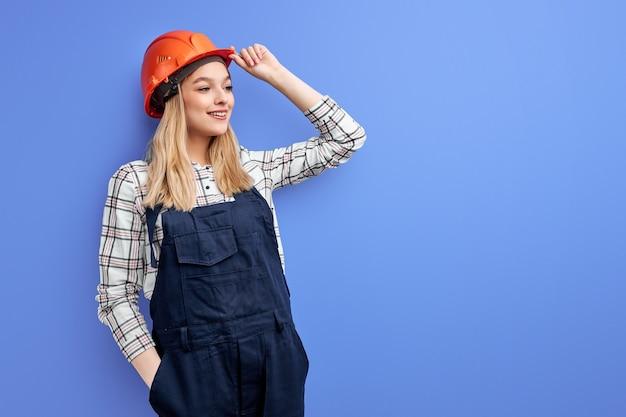 Mulher de negócios arquiteta com capacete laranja encostada na parede azul, jovem mulher branca com uniforme de macacão trabalha como engenheira construtora