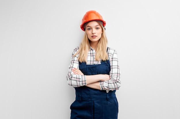 Mulher de negócios arquiteta com capacete laranja encostada na parede branca, jovem mulher branca com uniforme de macacão trabalha como engenheira construtora